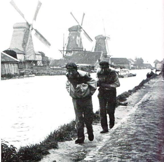 Wat een job ,Een tweetal jagers trekt een vrachtschuit langs het jaagpad van de Rotterdamse Schie. Op de achtergrond de houtzaagmolens Bruinvis, Jacobus en Nieuwe Werklust van de houthandel Van Stolk. De foto dateert uit 1906