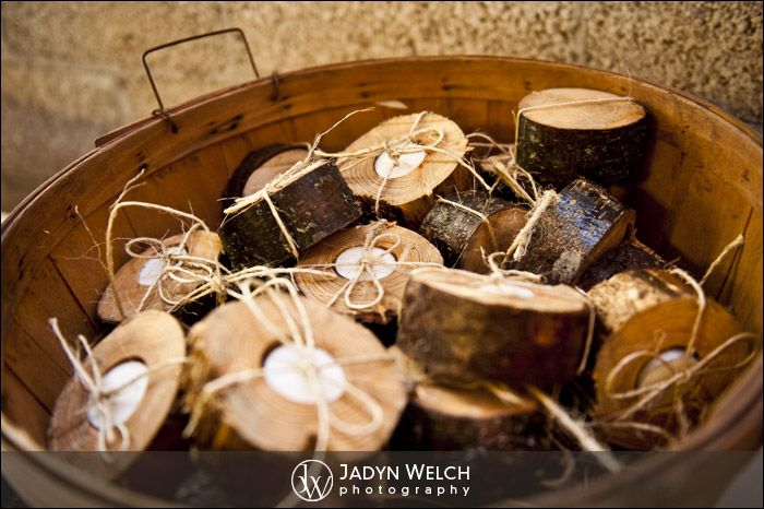cute wedding favors  cut logs with candle inside tied with raffia and presented in an apple basket!