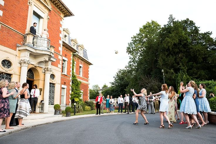 Bride throws bridal bouquet from balcony. Fetcham Park wedding venue Surrey Wedding Photographer © Fiona Kelly Photography