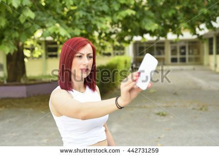 Beautiful young redhead woman taking selfie with her smartphone