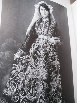 A women wearing a traditional Turkish wedding dress in red velvet and embellished with gold embroidery.