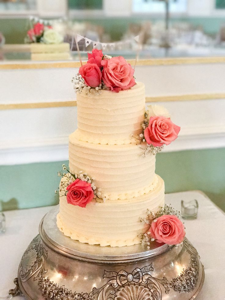 Three tiers soft-iced wedding cake with fresh coral roses