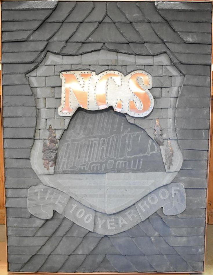 Roofing slate hand cut to make a slate logo with copper