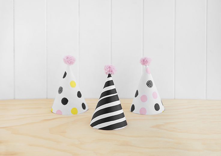 Find our free downloadable, printable template for DIY paper Party Hats with mini pompoms. They're the perfect, easy decoration idea for your next birthday party or celebration.