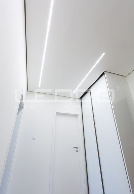 Minimalist design and LED line lights in the apartment. Elegant and simple plasterboard ceiling with narrow aluminium LED profiles and slim LED strip. The result is an elegant and modern interior.