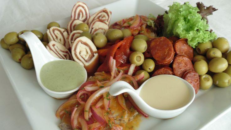 Antipasto fusión: Jamón del país en cubitos, Roll de jamón serrano con queso crema, Salteado de choricillo de Sarta, Pimientos asados, Mix de aceitunas rellenas, Salsas criolla, huancaína y ocopa.