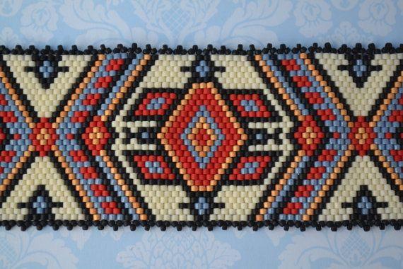 Peyote impar cuenta fue utilizado en la fabricación de esta pulsera con cuentas. Los colores son rojo, azul, oro, negro y crema, con delicas Miyuki. El cierre es un cierre de palanca plateada cobre de Tierracast. El borde está terminado con puntilla en negro. La pulsera mide 7 pulgadas de largo y 1 y 7/8 pulgadas de ancho. El diseño fue creado por Sig-Wynne Evans, basado en un patrón de bordado ucraniano.  Para encontrar el tamaño de la pulsera, sólo tiene que añadir el tamaño de su muñeca…