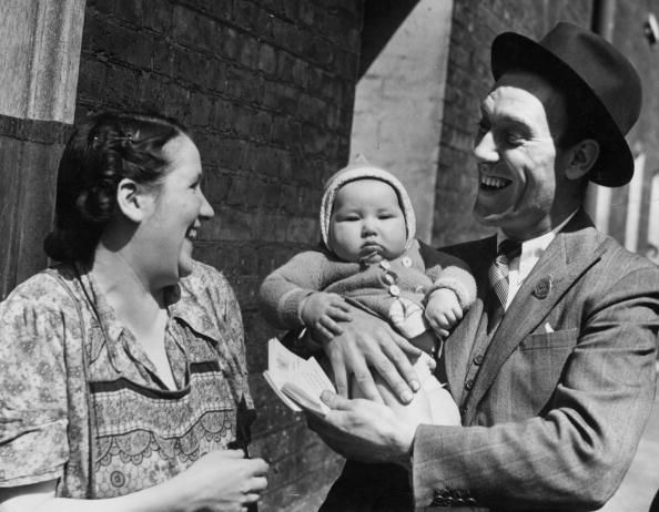 29th May 1942: English comedian Tommy Trinder ( 1909 - 1989) holding a Stepney mother's baby during a tour to obtain 500 war Savings street groups in London's East End. (Photo by Fred Morley/Fox Photos/Getty Images)