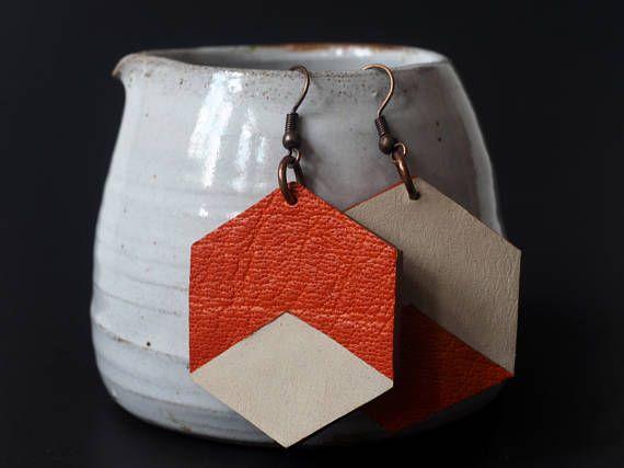 Boucles doreilles faites à la main à Montréal avec du cuir de buffle orange et du nubuck de buffle blanc. Les cotés sont teint en brun. La quincaillerie est de couleur cuivre. Ces boucles doreilles sont très légères. Mesures: Largeur 3.5cm Hauteur 4 cm