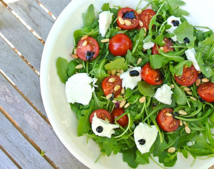 Een gezonde Italiaanse salade met rucola, mozzarella, cherrytomaatjes, pijnboompitjes en crema di balsamico.