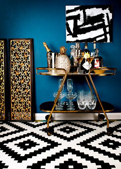 Stunning styling featuring navy blue walls, bold tile floors, black and white art and a gold gilt bar cart stacked with crystal and old-fashioned decanters | Photos by Eleanor Baines Photography