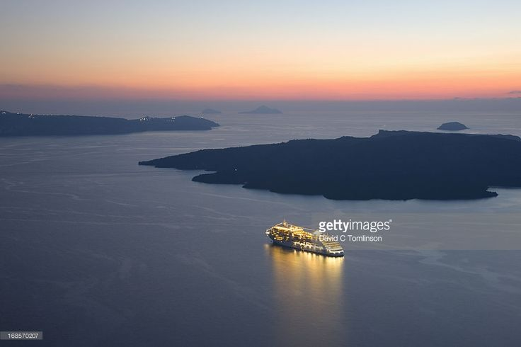 View from clifftop over the caldera after sunset, illuminated cruise ship anchored off the volcanic island of Nea Kameni, Fira, Santorini, Thira (aka Thera), Cyclades Islands, South Aegean, Greece, Europe.
