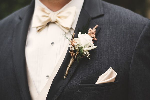 Groom in dark gray suit, ivory silk bow tie + matching pocket square and ivory rose boutonniere {Brit Jaye Photography}