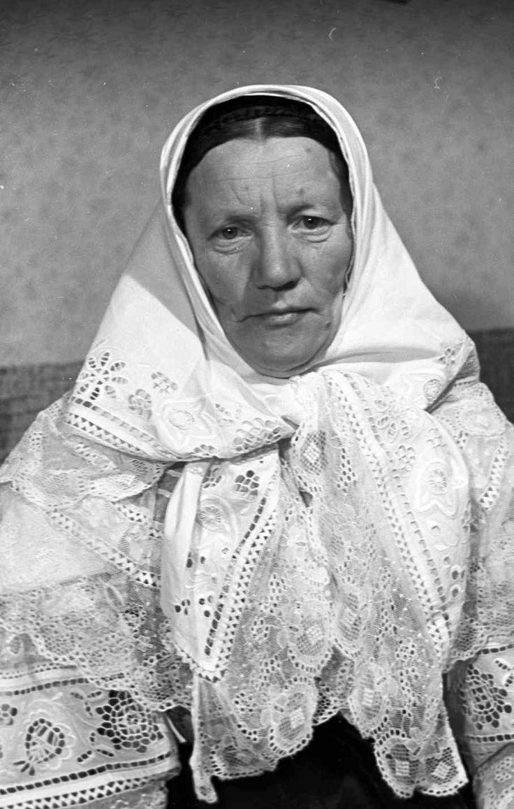 Doľany, okres Pezinok Žena v letnom sviatočnom odeve, ktorý sa nosil do 30. rokov 20. storočia. Rukávce sú s bielou výšivkou a bielou vláčkovou čipkou. Brokátový živôtik, veľký krezel z tylu s vláčkovou čipkou, biela šatka s výšivkou a vláčkovou čipkou,