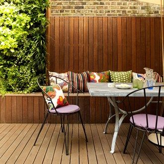 This stylish all-weather area uses matchboard planks, which flow up the wall to create a bench for the table, and a planting area for the living wall
