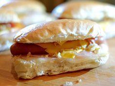 Broodje hotdog met bacon, cheddar en gebakken uitjes