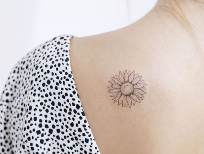 petit tatouage femme épaule, fleur, tournesol, dessin graphique, aux contours noirs élégant