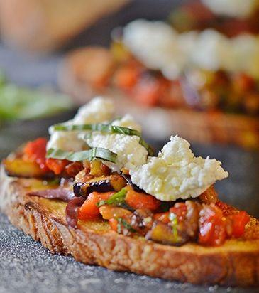 Σ' ένα ταψί στρώνουμε τις φέτες του ψωμιού. Κόβουμε τη μία σκελίδα σκόρδου στη μέση, τρίβουμε τις φέτες ψωμιού και τις αλείφουμε με λίγο ελαιόλαδο.