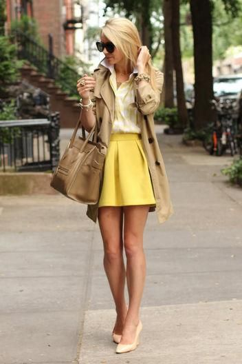 Fashion blogger Blair Eadie in a yellow skirt and top, trench coat, and Celine bag