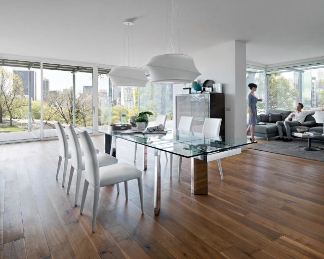 une table extensible en verre et acier inox et des chaises blanches et élégantes