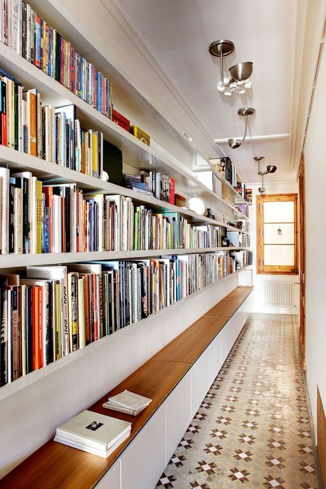 Ce long corridor évite l'écueil de la zone de passage stérile en s'imposant, non seulement comme un espace de rangement pour les livres, mais aussi un espace de lecture grâce au banc en bois blond qui court sur toute sa longueur.