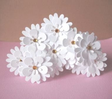 All white paper flowers. 3 layers of punches. Bling in the center.