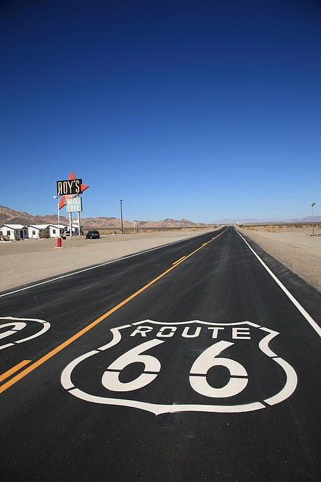 Route 66 through the desert town of Amboy, California. The famous Rt. 66 shield is painted on the old road outside Roy's Cafe.