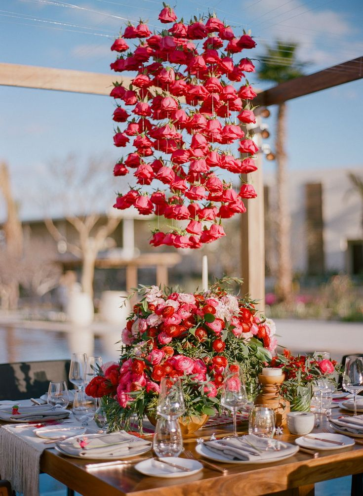 A chandelier of red roses suspended over a lush floral