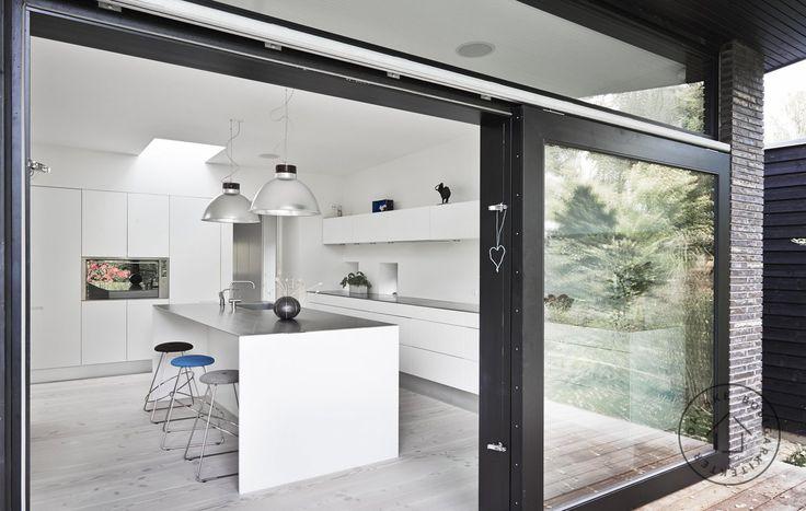 Køkken med store glasskydedøre og udgang til terrassen. Arkitekt maa Werner Mathies/Danske BoligArkitekter.
