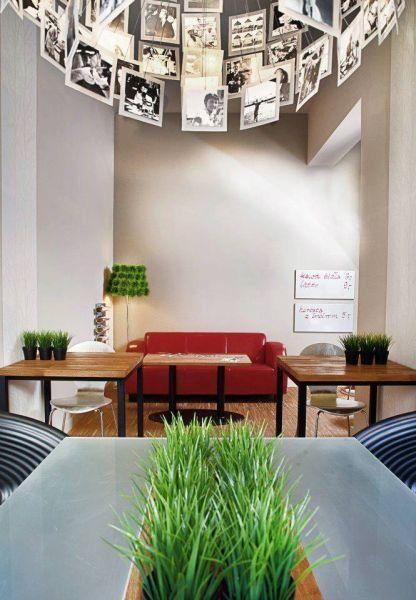 Resto-Bar. Lampa ze zdjęciami i zieleń wkomponowana w stół.