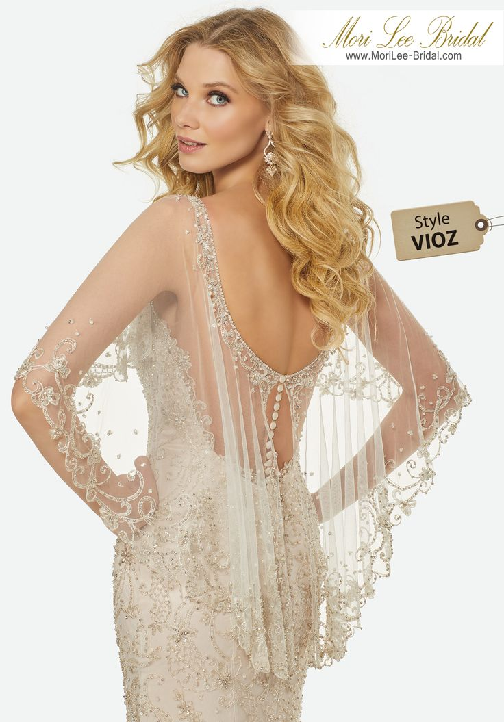 Style VIOZ MADELINE WEDDING DRESSIntricately Beaded Embroidery on a V-Neck, Slim Tulle Gown with Dramatic, Beaded Tulle Modified Capelet.Colors; IVORY/SILVER, IVORY/BLUSH/SILVER