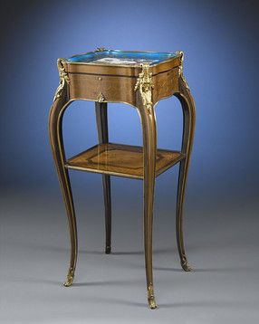 "This stunning table ambulante is attributed to the Durand Dynasty of French cabinetmakers. Luxurious hardwoods, hand-painted porcelain and bronze ormolu distinguish this elegant piece. The porcelain tray is marked with interlaced L and letters AA in blue underglaze on the underside. The top has been removed to reveal pencil inscriptions ""1913/Paris"" and ""Devaus."" Dated 1913"