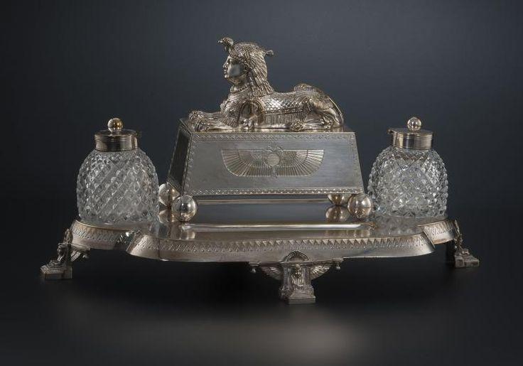 Encrier de bureau de forme polylobée en métal argenté, à 2 godets en verre taillé. Décor gravé de frise de chevrons et figure de sphinx, larg. 47 cm