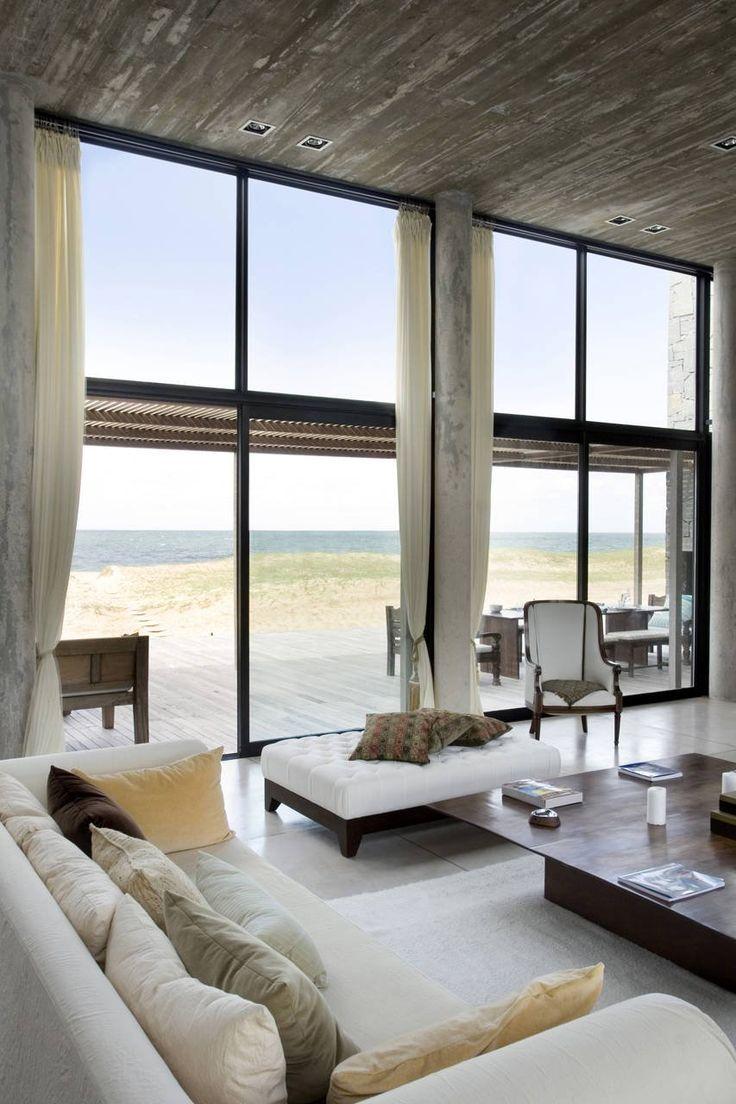 Full height windows with the pergola height carefully placed at mullion height. Estudio Martin Gomez Arquitectos designed the La Boyita house in Punta del Este, Uruguay.