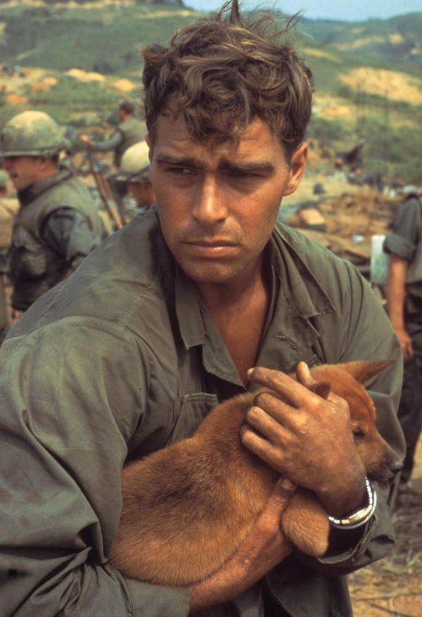An American soldier cradles a dog while under siege during the Battle of Khe Sanh, Vietnam, 1968