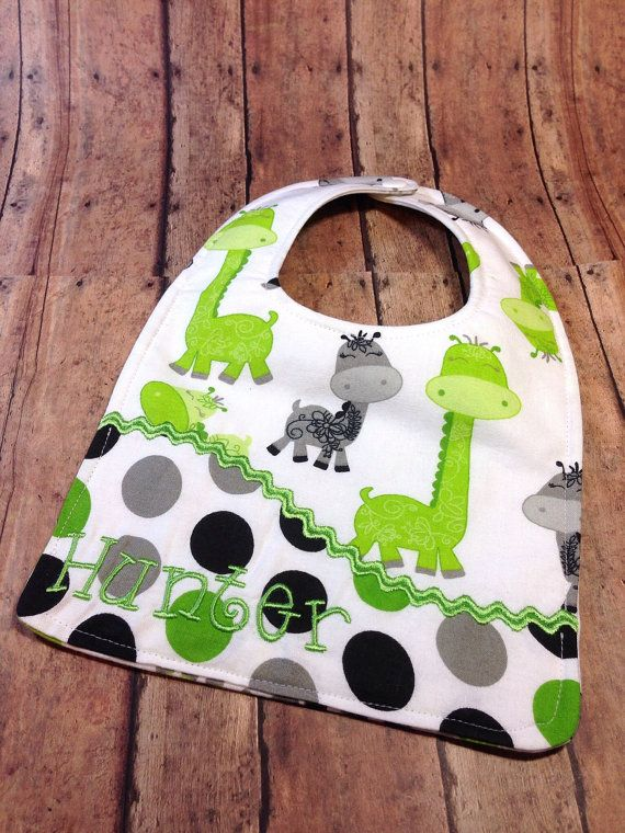 This listing is for one personalized baby bib. This would make a great shower gift or new mommy/grandma gift.  The front is in an adorable giraffe print and a grey, green and black dot print. The back is the giraffe print. There is a layer of absorbent flannel in the middle. The rick rack and font are in green - just let me know if you would like it in a different color. I have lots of different fabrics! Please convo me if you would like a different fabric combo. I love custom orders! ;)…