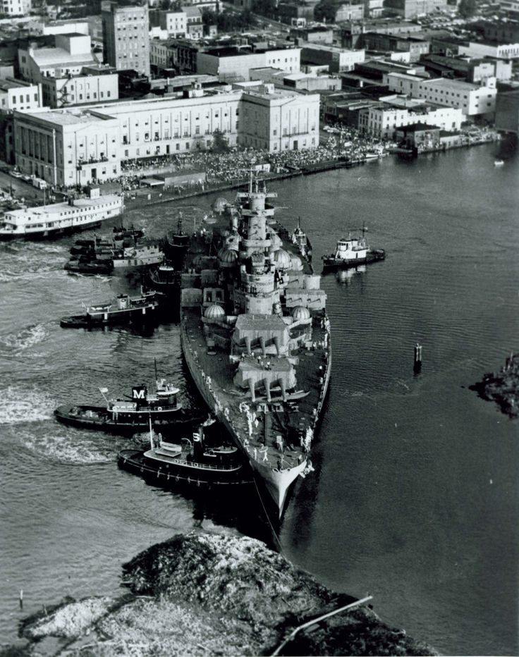 Tugs nudging the Battleship NORTH CAROLINA into berth upon her arrival in Wilmington in 1961