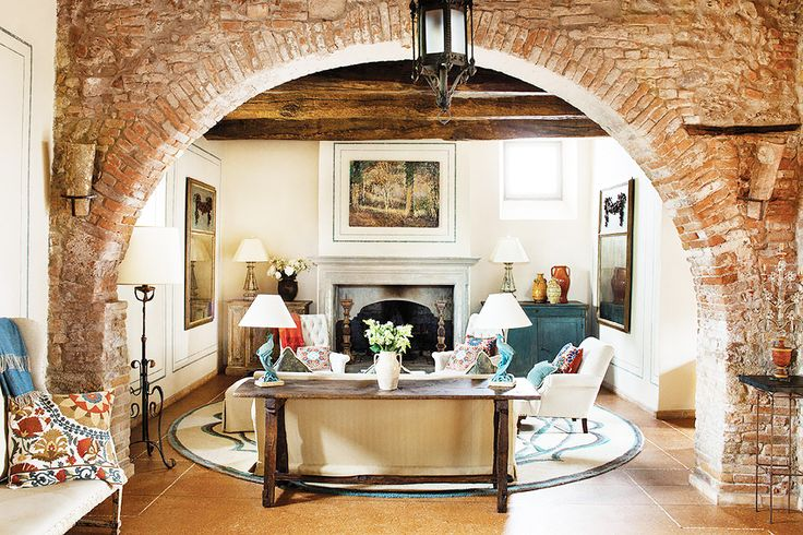 This 12th-century farmhouse is taken to new heights of chic, with century-old olive trees, exposed beams, brick arches, and beautifully tailored European furniture.
