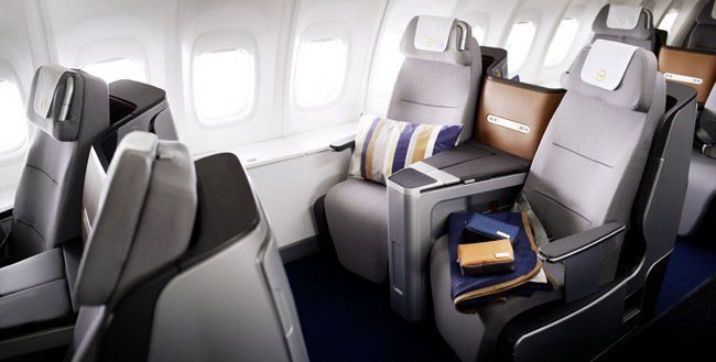 A pillow, a blanket and Lufthansa amenity kits are lying on the business class seats of a 747-8