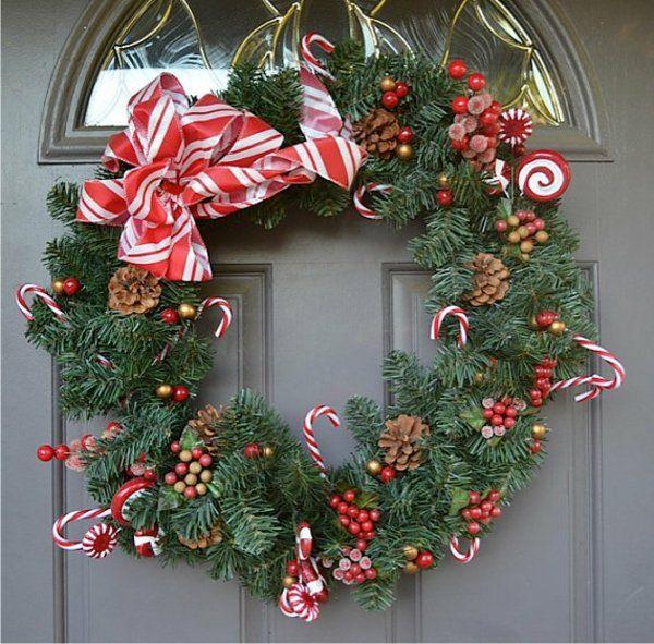 une couronne de Noël DIY verte de branches de pin décorée de pommes de pin et un ruban
