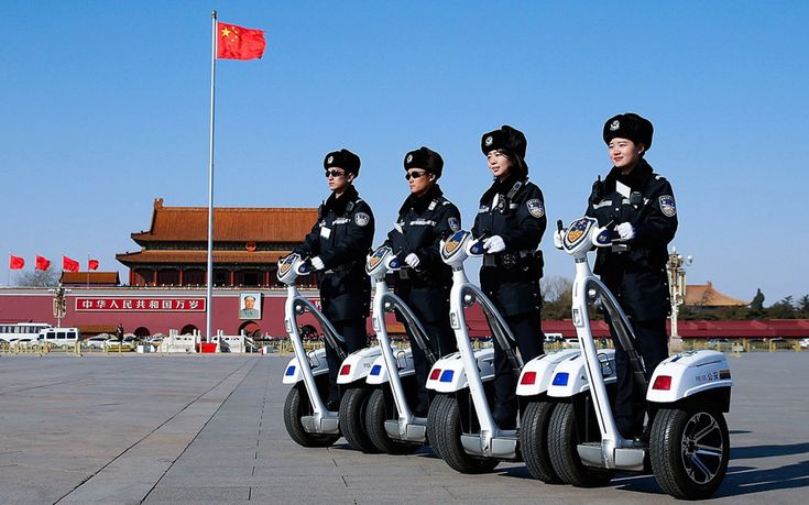 Police officers on motorised vehicles patrol at Tiananmen Square during the opening session of the Chinese People's Political Consultative Conference in Beijing, China