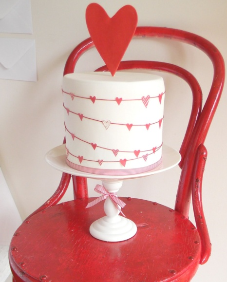 This cute wedding cake adorned with red hearts is perfect for a Valentine's Day wedding.