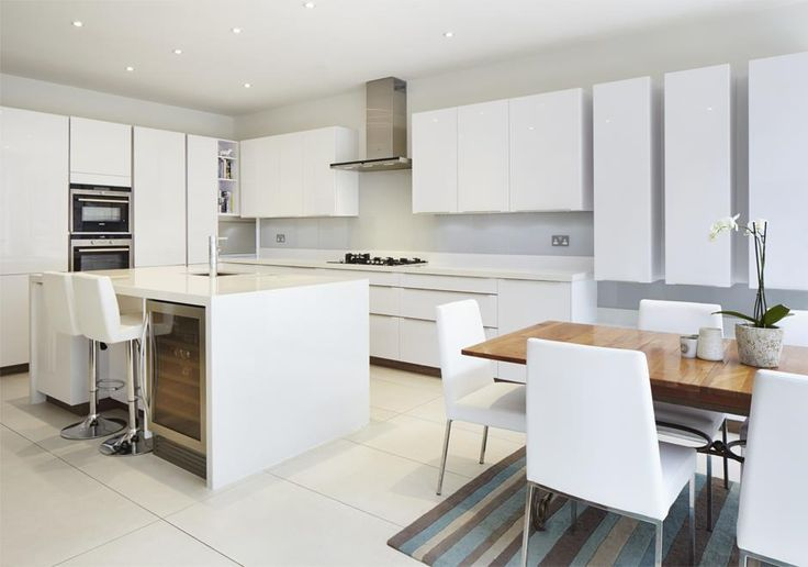 Open plan kitchen and dining room in this Kingston new build home. The clean white lines tie the space together and even hide a wine fridge under the central island.