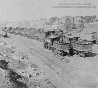 This image depicts locomotives sitting idle at B Railroad. During the Great Railroad Strike of 1877, the railroad industry came to a screeching halt because not only were the majority of railroad workers on strike, but most railroads in this area at the time attained some sort of extensive damage (whether it be destroyed railcars or uprooted railroad track). In the end, millions of dollars worth of damage was attained by the railroad industry of the east.