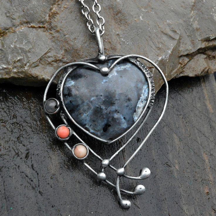 Srdce+plné+tajemství+Šperkové+srdíčko+je+vyrobené+ze+zvláštního+kamene+zvaného+Larvikit.+Zdobené+je+drobnými+korálky+korálu+a+krystalu.+Larvikin+je+šedavé+barvy+s+odlesky+jako+by+do+stříbrna.+Něco+jak+slída,+když+se+leskne+v+kameni.+Sám+kámen+je+pozoruhodný,+alespoň+pro+mne.+Přitahuje+oči.+Velikost+šperku+bez+úchytky+je+5,5cm+x+4,5cm.+Zavěšen+je+na+řetízku+o...