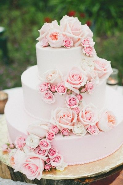 A traditional three tiered wedding cake with rose quartz roses spilling down the sides.: