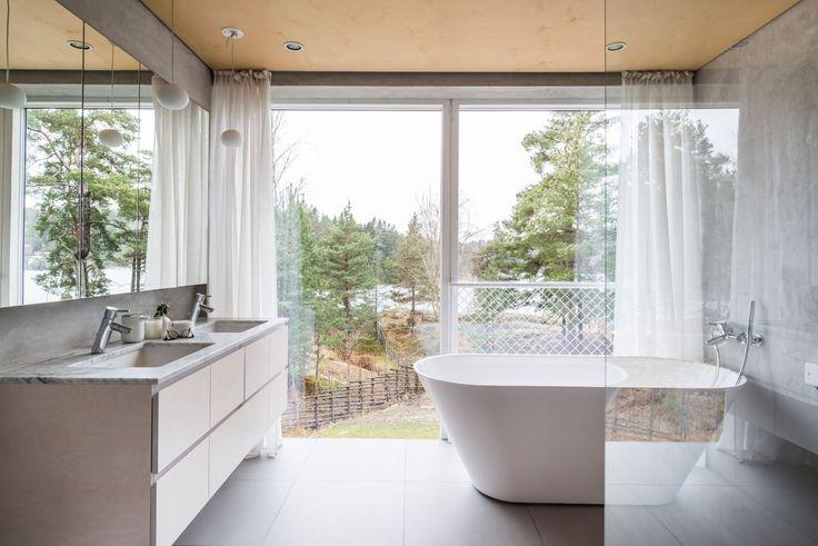 Bad med vindusvegg og detaljer i marmor, tre og betong.