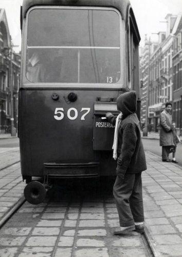 Jaren 50. De posterijen hebben brievenbussen aangebracht op trams en een jongen post een brief. Nederland, Amsterdam, 1958.