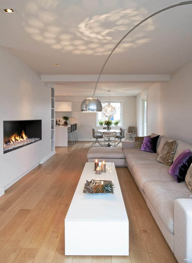 """Møblene er godt tilpasset det smale rommet. Den lange sofaen og salongborddet passer fint inn og fremhever rommets karakter. Lampen over bordet tegner en elegant bue i luften, og skinnet i taket skaper dynamikk. Riktig belysning skaper variasjoner og kontraster slik at rommene unngår å bli """"flate"""" og """"tunge"""". Stålampe Arco med marmorfot og kromskjerm fra Expo Nova Møbelgalleri. Sofaen og puffen Freetown er fra Living. Salongbordet er tegnet av interiørarkitektene Haeg Holm."""