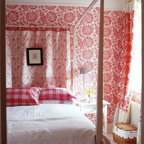 This bedroom with red and white floral wallpaper and matching curtains has a sleek four poster bed which adds a bit of modernity to the traditionally designed space. There red and white checkered pillowcases add a bit of French country flare. Love the framed florals above the bed and dainty bed-side lamp.